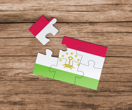 Tajikistan national flag on jigsaw puzzle. One piece is missing. Danger concept. Banque d'images