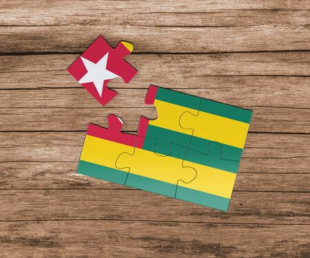Togo national flag on jigsaw puzzle. One piece is missing. Danger concept. Banque d'images
