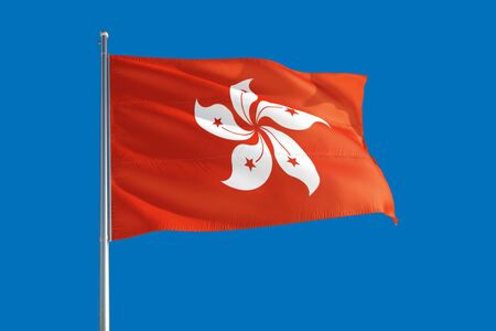 Hong Kong national flag waving in the wind on a deep blue sky. High quality fabric. International relations concept.