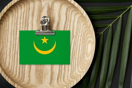 Mauritania flag tagged on wooden plate. Tropical palm leaves monstera on background. Minimal national concept.