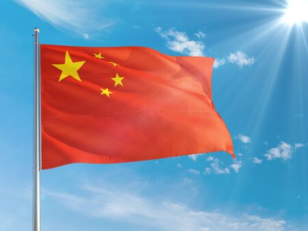 China national flag waving in the wind against deep blue sky. High quality fabric. International relations concept.