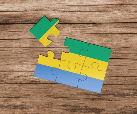 Gabon national flag on jigsaw puzzle. One piece is missing. Danger concept.