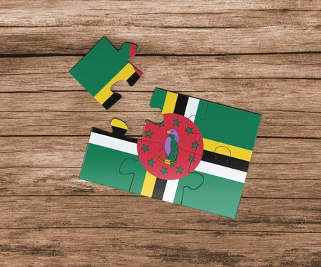 Dominica national flag on jigsaw puzzle. One piece is missing. Danger concept.