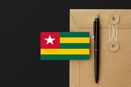 Togo flag on craft envelope letter and black pen background. National invitation concept. Invitation for education theme. Standard-Bild