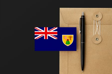 Turks And Caicos Islands flag on craft envelope letter and black pen background. National invitation concept. Invitation for education theme.