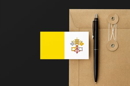 Vatican City flag on craft envelope letter and black pen background. National invitation concept. Invitation for education theme.