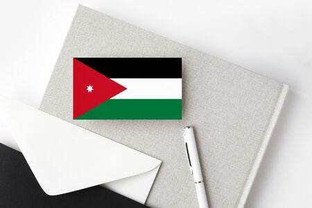 Jordan flag on minimalist letter background. National invitation envelope with white pen and notebook. Communication concept.