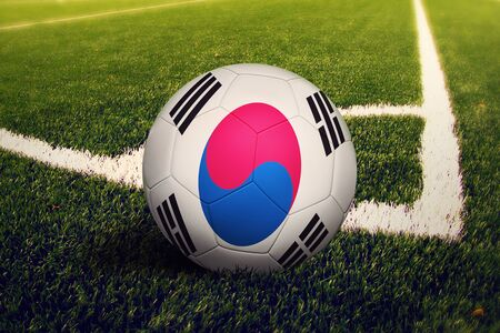 South Korea flag on ball at corner kick position, soccer field background. National football theme on green grass.