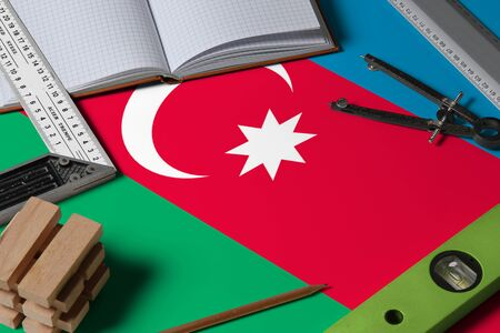 Azerbaijan national flag on profession concept with architect desk and tools background. Top view mock-up.