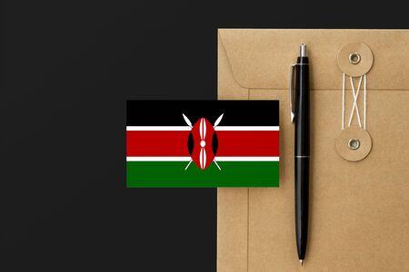 Kenya flag on craft envelope letter and black pen background. National invitation concept. Invitation for education theme.