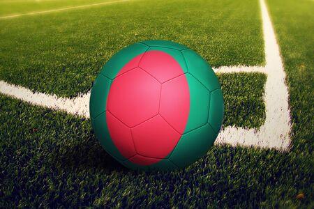 Bangladesh flag on ball at corner kick position, soccer field background. National football theme on green grass.