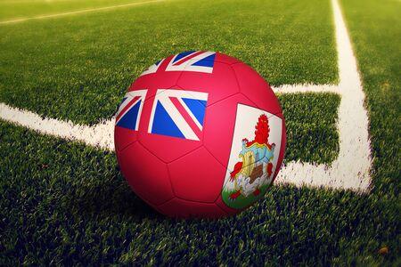 Bermuda flag on ball at corner kick position, soccer field background. National football theme on green grass.