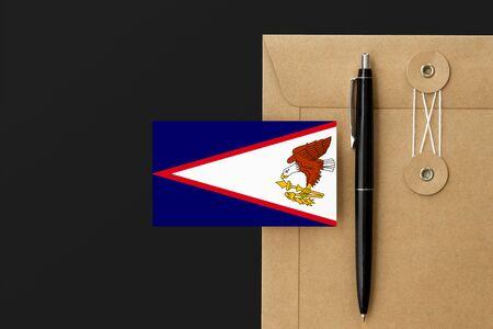 American Samoa flag on craft envelope letter and black pen background. National invitation concept. Invitation for education theme.