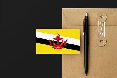 Brunei flag on craft envelope letter and black pen background. National invitation concept. Invitation for education theme.