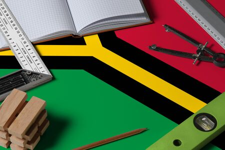 Vanuatu national flag on profession concept with architect desk and tools background. Top view mock-up.