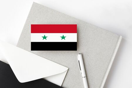 Syria flag on minimalist letter background. National invitation envelope with white pen and notebook. Communication concept. Banco de Imagens