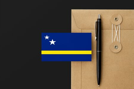 Curacao flag on craft envelope letter and black pen background. National invitation concept. Invitation for education theme.