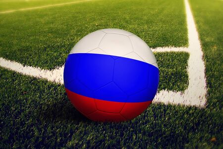 Russia flag on ball at corner kick position, soccer field background. National football theme on green grass.