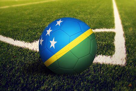 Solomon Islands flag on ball at corner kick position, soccer field background. National football theme on green grass.