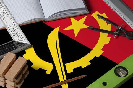 Angola national flag on profession concept with architect desk and tools background. Top view mock-up.
