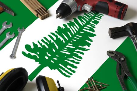 Norfolk Island flag on repair tool concept wooden table background. Mechanical service theme with national objects. Stock Photo