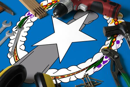 Northern Mariana Islands flag on repair tool concept wooden table background. Mechanical service theme with national objects. Reklamní fotografie