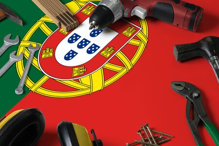 Portugal flag on repair tool concept wooden table background. Mechanical service theme with national objects.