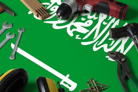 Saudi Arabia flag on repair tool concept wooden table background. Mechanical service theme with national objects.