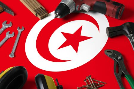 Tunisia flag on repair tool concept wooden table background. Mechanical service theme with national objects.