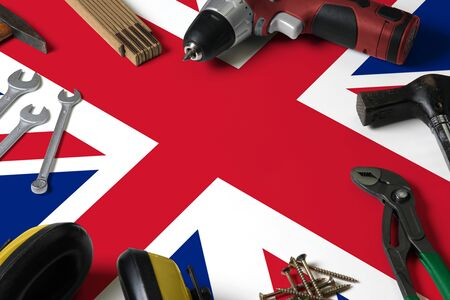 United Kingdom flag on repair tool concept wooden table background. Mechanical service theme with national objects.