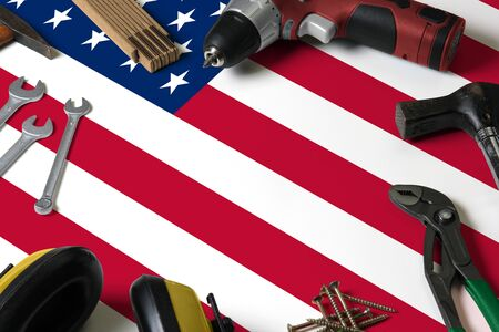 United States flag on repair tool concept wooden table background. Mechanical service theme with national objects.