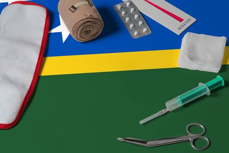 Solomon Islands flag with first aid medical kit on wooden table background. National healthcare system concept, medical theme.