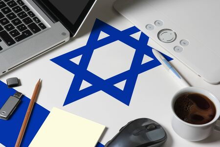 Israel national flag on top view work space of creative designer with laptop, computer keyboard, usb drive, graphic tablet, coffee cup, mouse on wooden table.