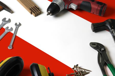 Austria flag on repair tool concept wooden table background. Mechanical service theme with national objects.