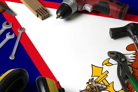 American Samoa flag on repair tool concept wooden table background. Mechanical service theme with national objects.