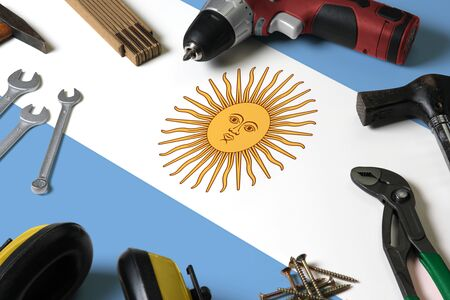 Argentina flag on repair tool concept wooden table background. Mechanical service theme with national objects. Reklamní fotografie