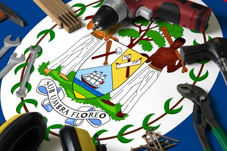 Belize flag on repair tool concept wooden table background. Mechanical service theme with national objects.