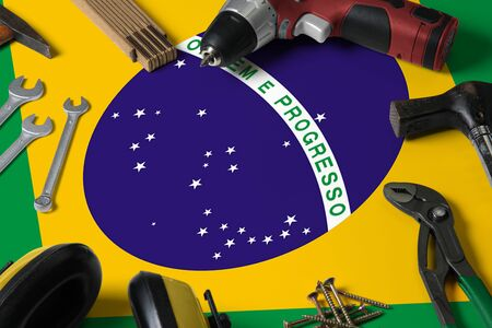 Brazil flag on repair tool concept wooden table background. Mechanical service theme with national objects.