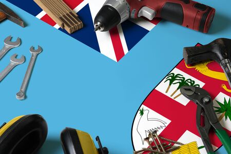Fiji flag on repair tool concept wooden table background. Mechanical service theme with national objects. Reklamní fotografie