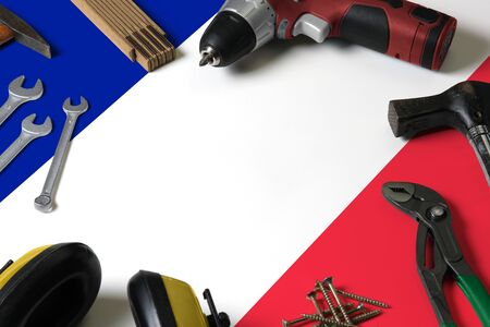 France flag on repair tool concept wooden table background. Mechanical service theme with national objects.