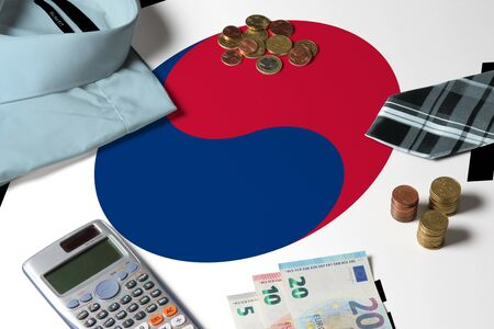 South Korea flag on minimal money concept table. Coins and financial objects on flag surface. National economy theme.