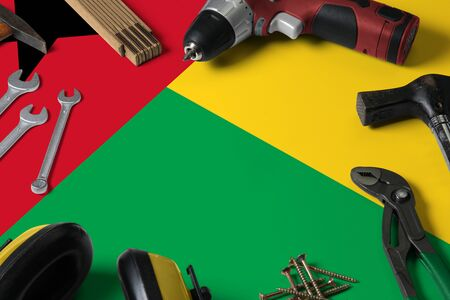 Guinea flag on repair tool concept wooden table background. Mechanical service theme with national objects.