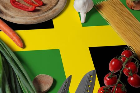 Jamaica flag on fresh vegetables and knife concept wooden table. Cooking concept with preparing background theme. Banque d'images