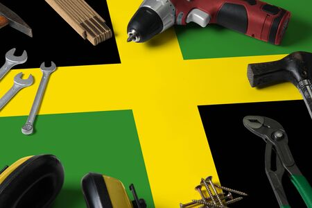 Jamaica flag on repair tool concept wooden table background. Mechanical service theme with national objects.