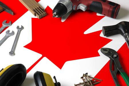 Canada flag on repair tool concept wooden table background. Mechanical service theme with national objects.