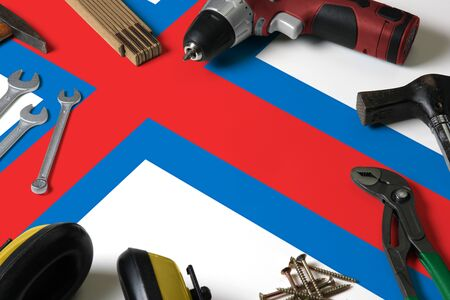 Faroe Islands flag on repair tool concept wooden table background. Mechanical service theme with national objects. Reklamní fotografie