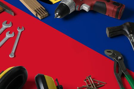 Liechtenstein flag on repair tool concept wooden table background. Mechanical service theme with national objects.