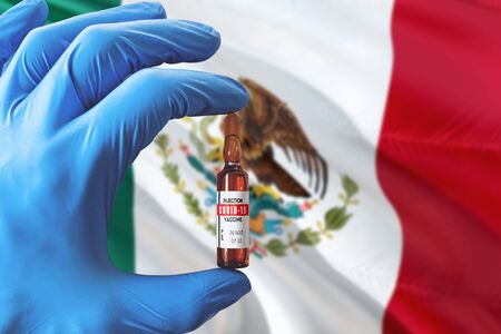 Mexico flag with Coronavirus Covid-19 concept. Doctor with blue protection medical gloves holding a vaccine bottle. Epidemic Virus, Cov-19, Corona virus outbreaking.