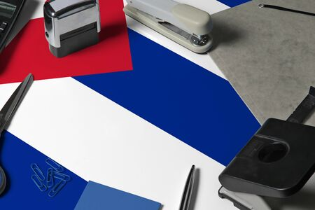 Cuba flag with office clerk workplace background. National stationary concept with office tools.