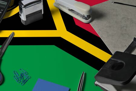 Vanuatu flag with office clerk workplace background. National stationary concept with office tools.